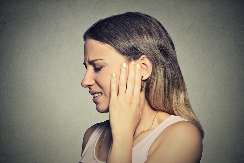 young woman with ear pain holds the side of her jaw