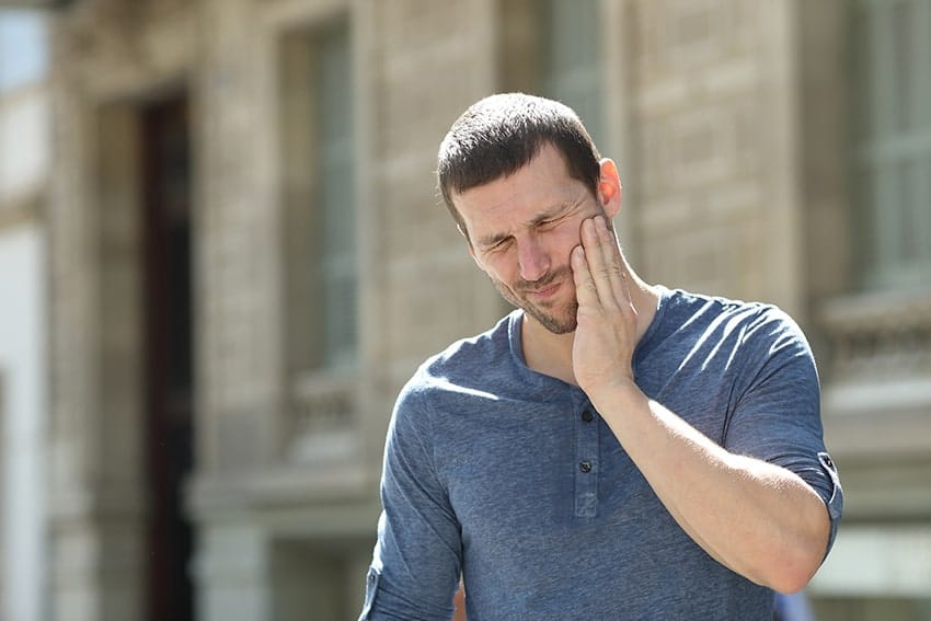 Athletic man holding his jaw in pain