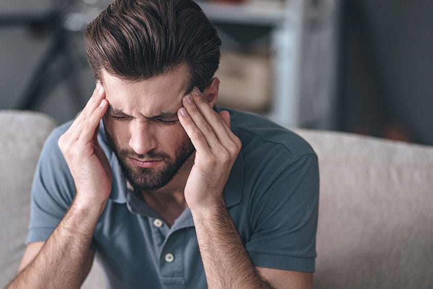man suffering from a migraine headache sits on his couch, rubbing her forehead