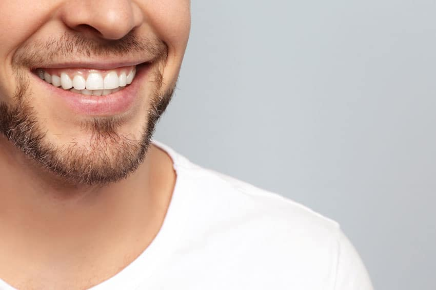closeup of a male's mouth showing a thin beard and large smile