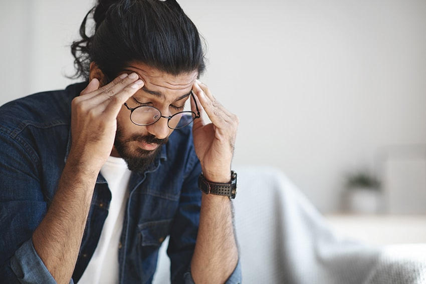 hipster with beard suffering from a migraine headache